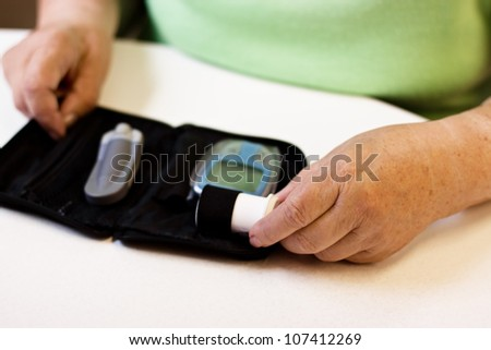 hands of senior with equipment of blood sugar test - stock photo