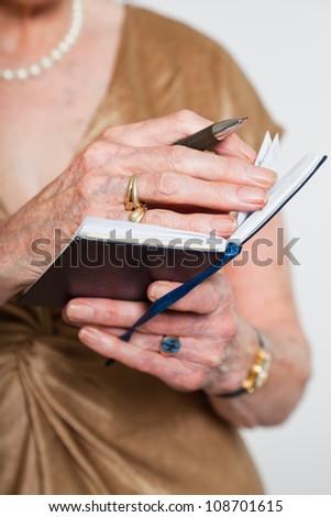 Hands of senior woman holding agenda. Studio shot on grey background. - stock photo