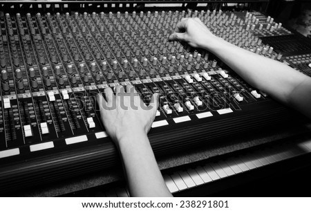 hands of sound engineer work on recording studio mixer, mixing board / black and white processed - stock photo