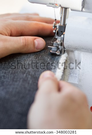 Hands of tailor working on a sewing machine with close up focus on a needle