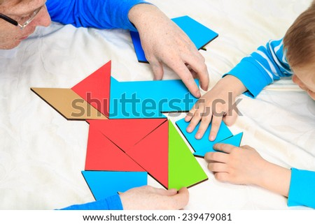 hands of teacher and child playing with geometric shapes, early learning - stock photo