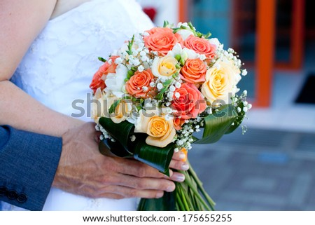hands of the bride and groom and beautiful wedding bouquet  - stock photo