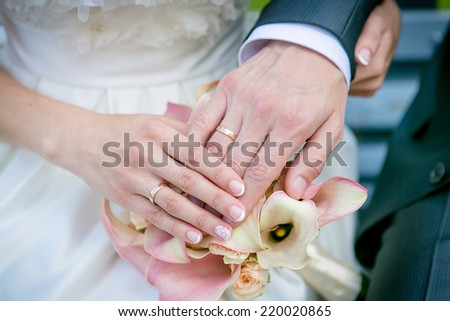 Hands of the bride and groom on the wedding bouquet - stock photo