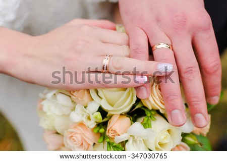 Hands of the bride and groom. Wedding bridal bouquet. Wedding rings.