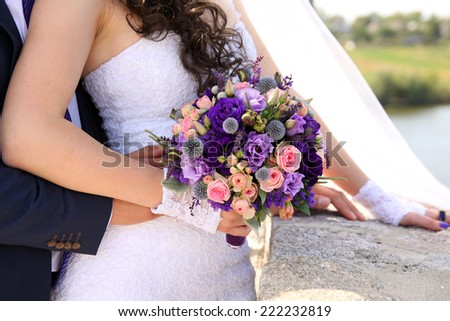 hands of the bride and groom with rings on a beautiful wedding bouquet - stock photo
