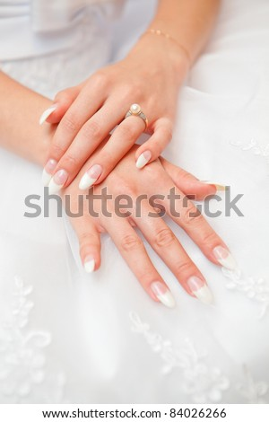 Hands of the bride with ornaments against a white dress