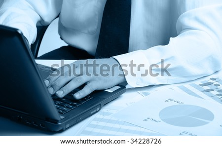 Hands of the businessman above the keyboard laptop. Blue color - stock photo