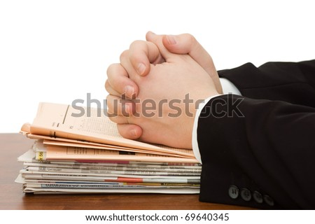 Hands of the businessman on a pile of newspapers - stock photo