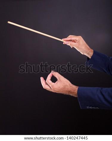 hands of the conductor on black background - stock photo
