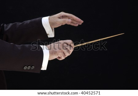 hands of the conductor, on black background - stock photo