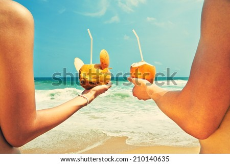 Hands of the couple with coconut drinks - stock photo