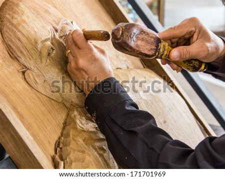hands of the craftsman carve a bas-relief. - stock photo