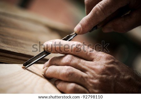 hands of the craftsman carve a bas-relief with a gouge - stock photo