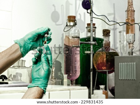 Hands of the doctors with green gloves filling a syringe - stock photo