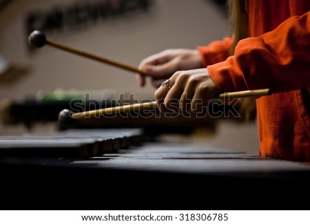 Hands of the girl playing the xylophone in dark colors - stock photo