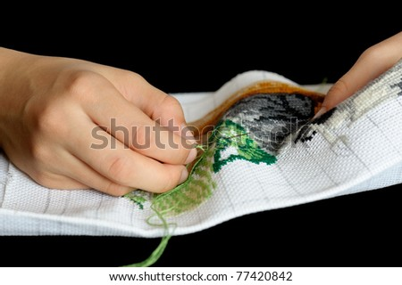 Hands of the girl working upon the embroidery, located on a black background. - stock photo