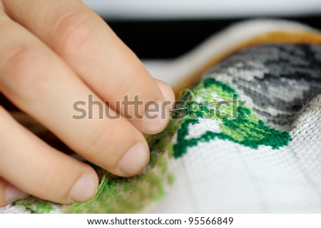 Hands of the girl working upon the embroidery, located on a black background - stock photo