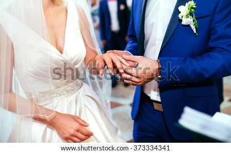 Hands of the groom and bride is wearing a ring on the finger on the day of the wedding ceremony. Gold, symbol, religion, love. - stock photo
