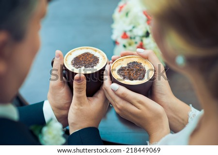 Hands of the groom and the bride and coffee cups on the table - stock photo