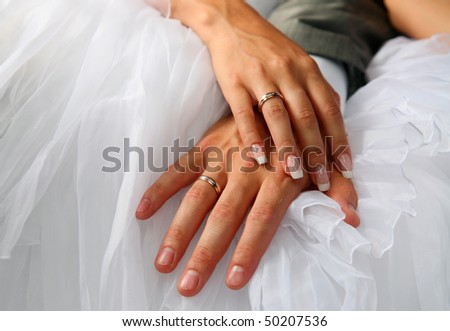 Hands of the groom and the bride with wedding rings - stock photo