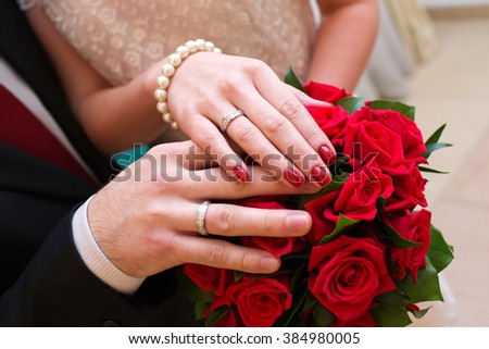 Hands of the groom and the bride with wedding rings and a wedding bouquet - stock photo