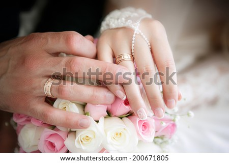 Hands of the groom and the bride with wedding rings and a wedding bouquet from roses - stock photo
