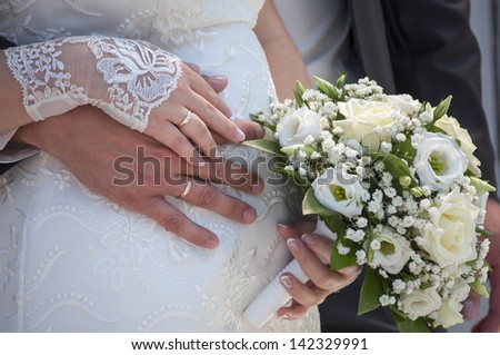 Hands of the groom and the bride with wedding rings and bouquet - stock photo