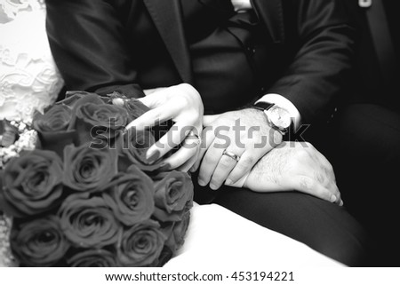 Hands of the groom and the bride with wedding rings on wedding bouquet - stock photo