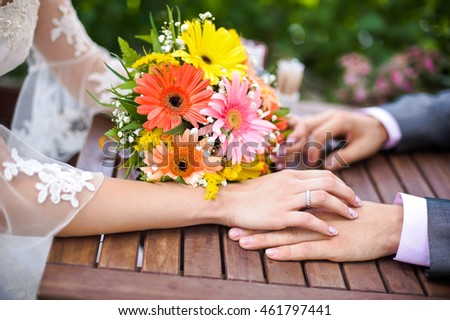 Hands of the groom, bride and bouquet