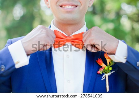 Hands of the groom holding a tie - stock photo