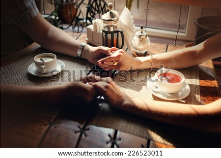 Hands of the guy and hand of the girl at a table with a cup of tea and a cup of coffee in cafe shop - stock photo