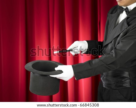 Hands of the magician with magic wand and top hat on stage. - stock photo