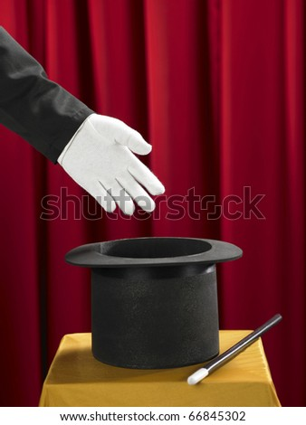 Hands of the magician with top hat and magic wand on stage. - stock photo