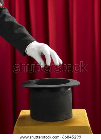 Hands of the magician with top hat on stage. - stock photo
