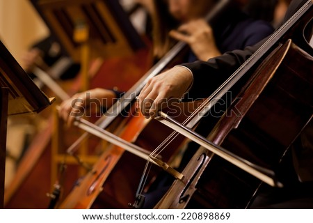 Hands of the man playing the cello  - stock photo