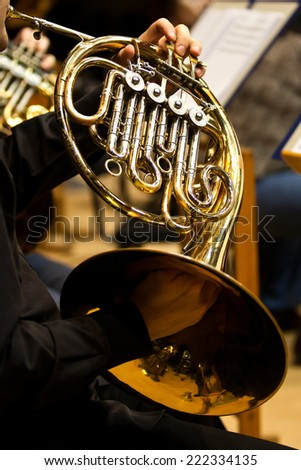 Hands of the man playing the French horn  - stock photo