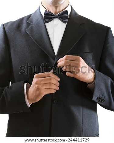 hands of the man who in a black tuxedo clasps a jacket button - stock photo