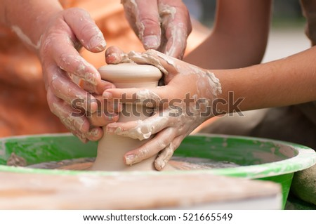 hands of the master Potter and a baby on pottery wheel