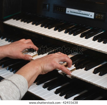 Hands of the musician on an organ keyboard - stock photo