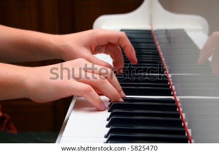 Hands of the musician playing on the piano