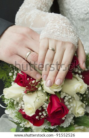 hands of the newlyweds with wedding rings on a bouquet of roses - stock photo