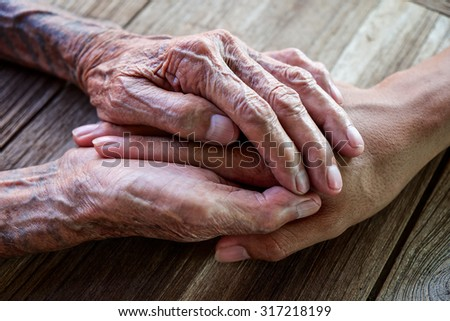 Hands of the old man and a young man