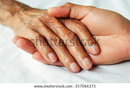 Hands of the old man and a young man on a white bed in a hospital. - stock photo