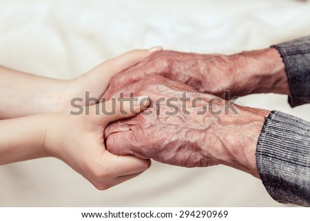 Hands of the old man and a young woman. toning - stock photo