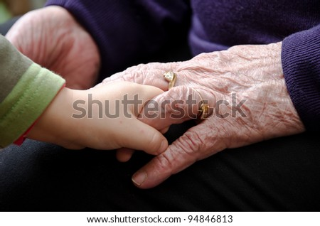 Hands of the old woman and child - stock photo