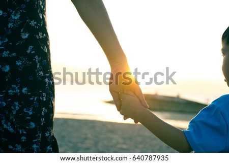 Hands of the parent and little child at beach under sunset