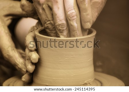 Hands Of The Potter And His Disciple - stock photo