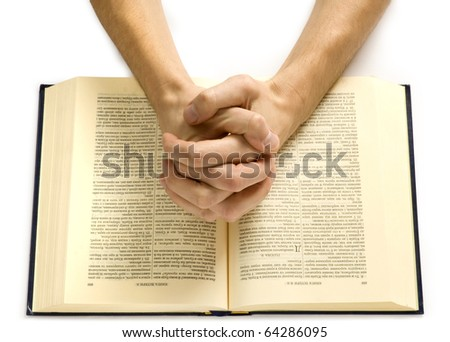 Hands of the praying man lie on the bible - stock photo