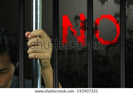 Hands of the prisoner on the prison - stock photo