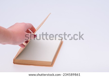 Hands of the woman opening new empty notebook beginning new life isolated on white background - stock photo